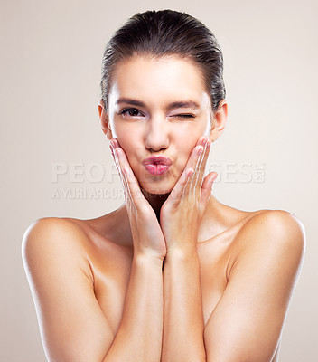 Buy stock photo Studio portrait of a beautiful young woman winking against a beige background