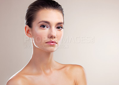 Buy stock photo Studio portrait of a beautiful young woman posing against a beige background