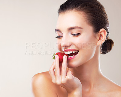 Buy stock photo Studio shot of a beautiful young woman eating a strawberry against a beige background
