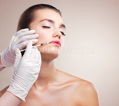 Buy stock photo Studio shot of a beautiful young woman getting her face injected by gloved hands against a beige background