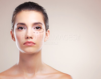 Buy stock photo Studio portrait of a beautiful young woman with cosmetic surgery markings on her face against a beige background