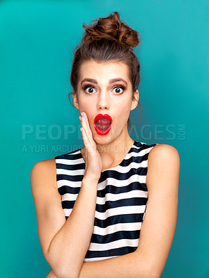 Buy stock photo Studio portrait of a beautiful young woman looking shocked against a turquoise background
