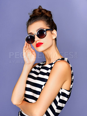 Buy stock photo Studio shot of a beautiful young woman wearing glasses while posing against a purple background