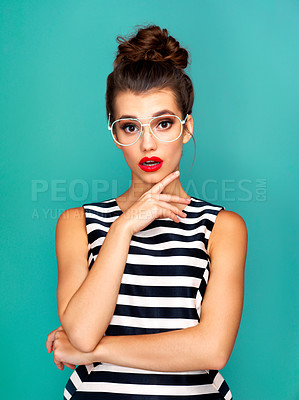 Buy stock photo Studio shot of a beautiful young woman wearing glasses while posing against a turquoise background