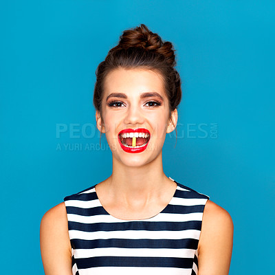 Buy stock photo Studio portrait of a beautiful young woman with a pill in her mouth against a blue background