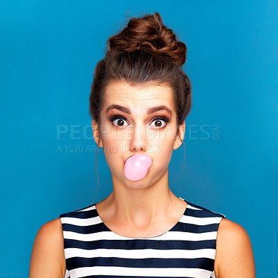 Buy stock photo Studio portrait of a beautiful young woman blowing bubblegum against a blue background