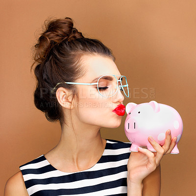 Buy stock photo Studio shot of a beautiful young woman kissing a piggybank against a bronze background