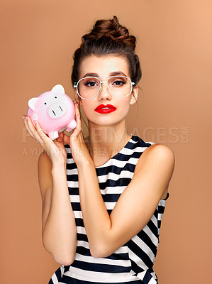 Buy stock photo Studio portrait of a beautiful young woman holding a piggybank against a bronze background