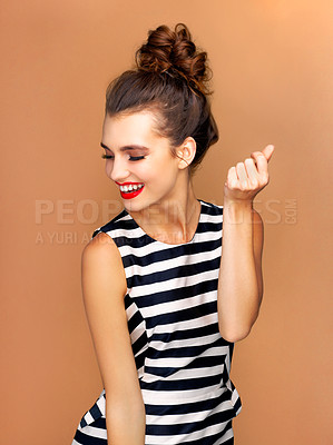 Buy stock photo Studio shot of a beautiful young woman dancing against a bronze background