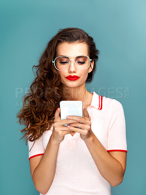 Buy stock photo Studio shot of a beautiful young woman using a cellphone against a turquoise background