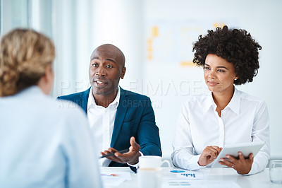 Buy stock photo Shot of a young man and woman meeting with a financial planner in a modern office