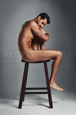 Buy stock photo Studio shot of a handsome young man sitting naked on a chair and looking sad against a grey background