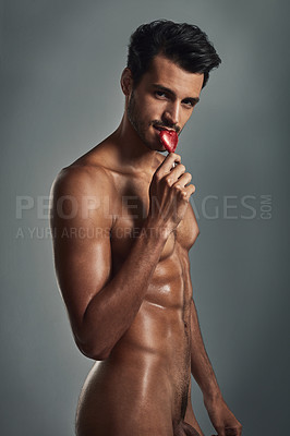 Buy stock photo Studio shot of a handsome young man eating a lolly in the nude against a grey background