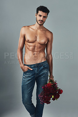 Buy stock photo Studio shot of a handsome and shirtless young man holding a bunch of roses against a grey background
