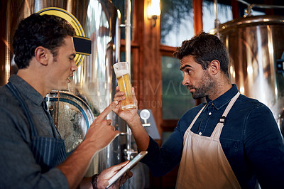 Buy stock photo Shot of two focused young male business owners testing out a fresh batch of beer inside of their beer brewery during the day