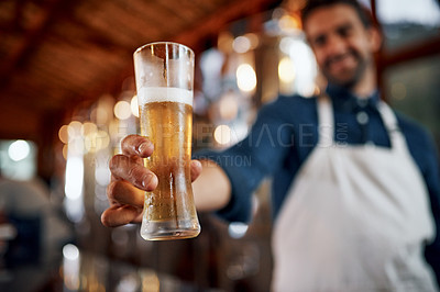 Buy stock photo Closeup of a cheerful young business owner holding up a glass of beer that he just poured inside of a beer brewery during the day