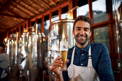 Buy stock photo Portrait of a cheerful young business owner holding up a glass of beer that he just poured inside of a beer brewery during the day