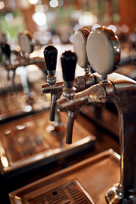 Buy stock photo Closeup of a couple of beer taps standing and waiting to be used inside of a beer brewery during the day