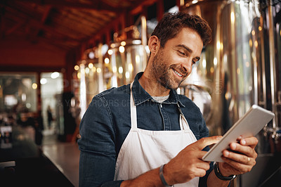 Buy stock photo Shot of a cheerful young barman browsing on a digital tablet while patiently waiting at the bar for customers inside of a beer brewery during the day