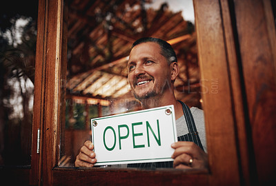 Buy stock photo Shot of a cheerful middle aged business owner holding up a sign saying