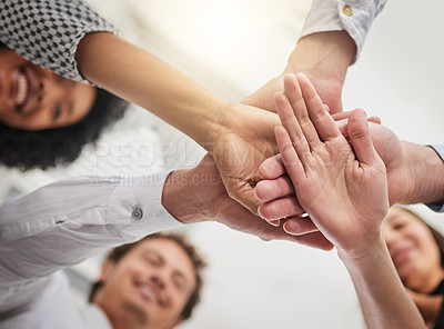 Buy stock photo Low angle shot of a group of colleagues joining hands in solidarity in a modern office