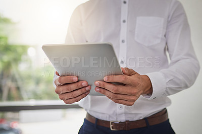 Buy stock photo Cropped shot of an unrecognizable businessman using a digital tablet in a modern office