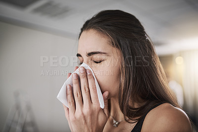 Buy stock photo Shot of a young woman blowing her nose