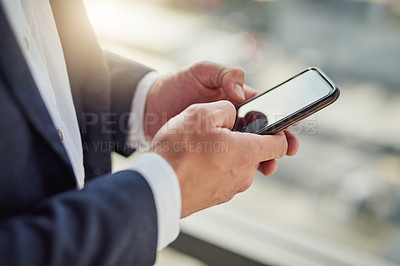 Buy stock photo Cropped shot of a businessman using a mobile phone in a modern office