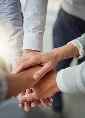 Buy stock photo Cropped shot of a group of colleagues joining hands in solidarity in a modern office