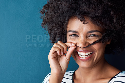 Buy stock photo Studio portrait of an attractive young woman making a moustache with her hair against a blue background