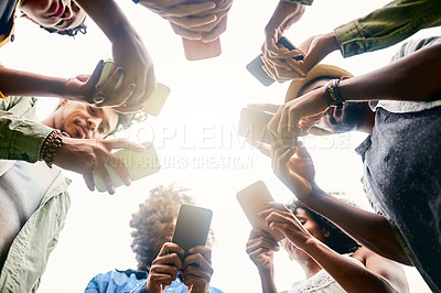 Buy stock photo Low angle shot of a group of friends using cellphones in a public park