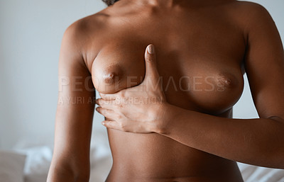 Buy stock photo Cropped shot of a young woman examining her breasts at home