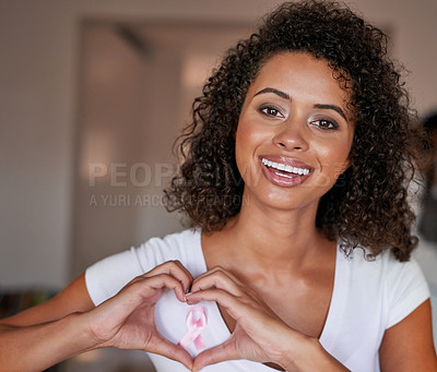 Buy stock photo Portrait of a beautiful young woman making a heart gesture over a pink breast cancer awareness ribbon