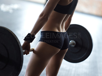 Buy stock photo Cropped shot of an unrecognizable woman lifting weights in the gym