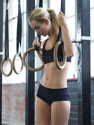 Buy stock photo Cropped shot of an attractive young woman working out with the rings in the gym