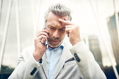 Buy stock photo Shot of a mature businessman looking stressed out while talking on a cellphone in the city