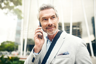 Buy stock photo Shot of a mature businessman talking on a cellphone in the city