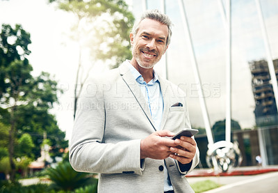 Buy stock photo Portrait of a mature businessman using a cellphone in the city