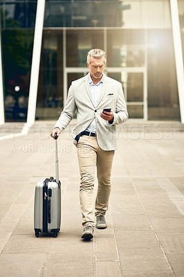Buy stock photo Shot of a mature businessman using a cellphone while walking with a suitcase in the city