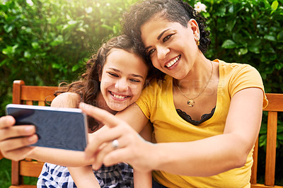 Buy stock photo Cropped shot of a young mother and her daughter taking selfies while sitting on a bench in the park
