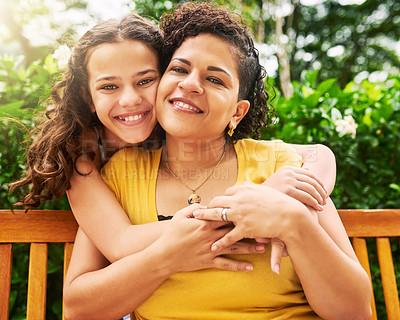 Buy stock photo Cropped portrait of an adorable young girl embracing her mother while out in the park