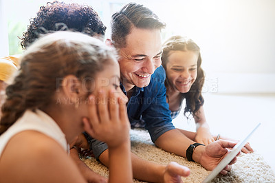 Buy stock photo Cropped shot of a young family of four looking at a tablet while sitting on the sofa at home
