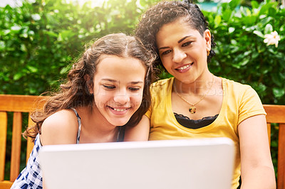 Buy stock photo Cropped shot of a young woman and her daughter using a laptop while sitting on a bench in the park