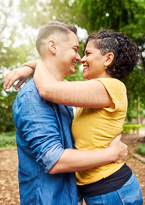 Buy stock photo Cropped shot of an affectionate young couple embracing while standing outside in the park