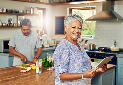 Buy stock photo Portrait of a mature woman using a digital tablet while preparing a meal at home with her husband