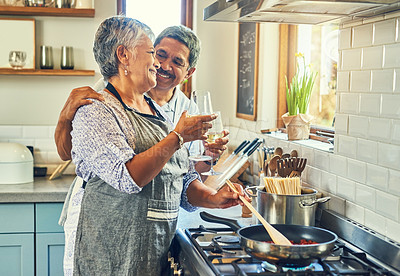 Buy stock photo Shot of a happy mature couple toasting with wine while cooking a meal together at home