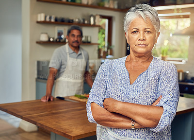 Buy stock photo Portrait of a mature woman looking upset after a fight with her husband who is cooking in the background