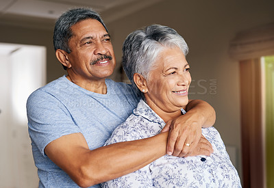 Buy stock photo Shot of a cheerful mature couple holding each other while looking outside through a window at home during the day