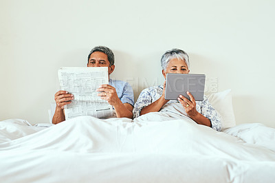 Buy stock photo Shot of a relaxed mature couple lying in bed while browsing on a digital tablet and reading the newspaper at home in the morning