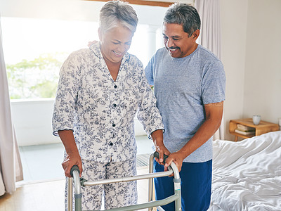 Buy stock photo Shot of a determined mature woman using a walking frame to walk with while being supported by her husband at home during the day